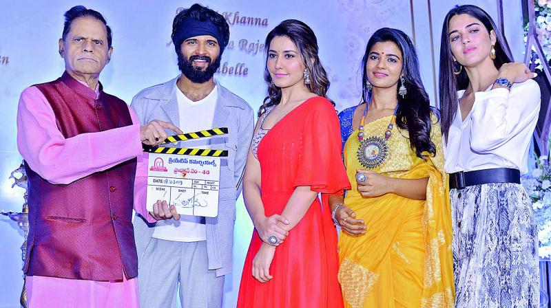 T. Subbarami Reddy sounding the clap board while Vijay Deverakonda, Raashi Khanna, Aishwarya Rajesh and Izabelle Leite pose at the film's launch.