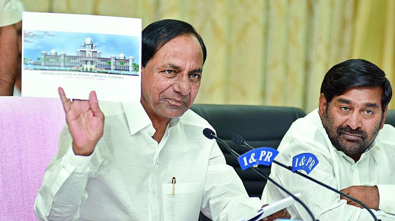 Chief Minister K. Chandrasekhar Rao holds an image of a building which he explained was not the plan for the new Assembly as education minister G. Jagadish Reddy looks on. Upon hearing of reports that the TS government wanted to construct a new Assembly, many people were sending him designs but nothing had been finalised, he said. (Photo: R. Surender Reddy)