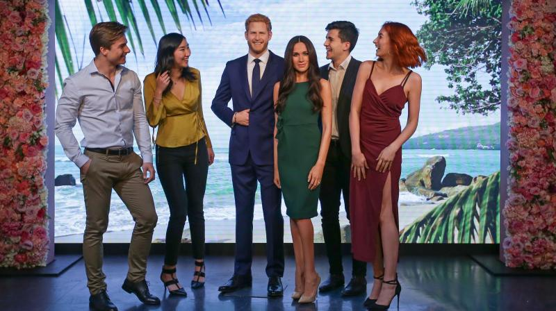 People pose alongside wax figures of Britain's Prince Harry and his US fiancee Meghan Markle during a photocall at Madame Tussauds in central London on May 9, 2018.(Photo: AFP)