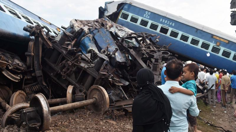 People looking at the wreckage of the rail compartments as workers are carrying out the repair work after Puri-Haridwar Utkal Express derailed in Khatauli near Muzaffarnagar on Saturday. (Photo: PTI)