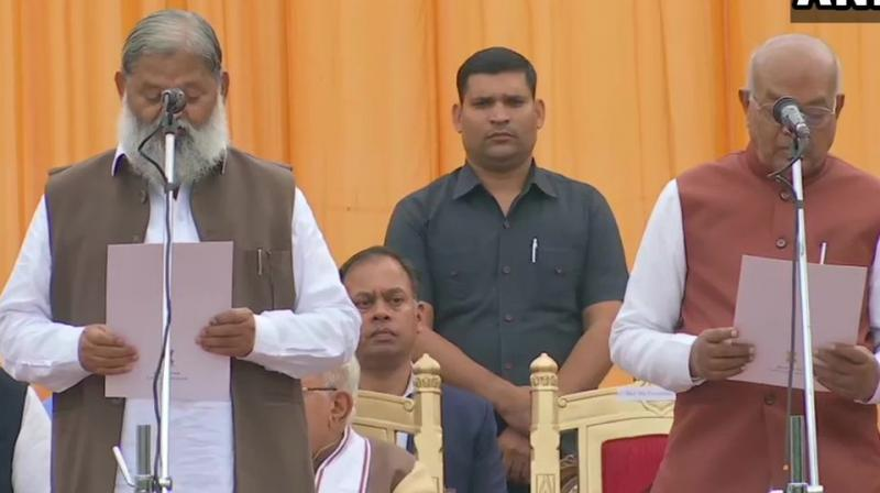 Haryana governor Satyadeo Narain Arya administered the oath to newly inducted ministers at a ceremony at the lawns of Raj Bhawan here. (Photo: ANI)