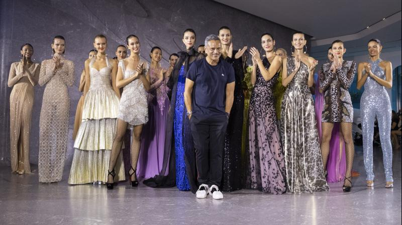 Designer naeem Khan takes a bow, posing with the models showcasing his clothes on the ramp. (Photo: AP)