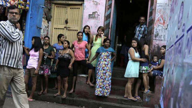 Women stand outside Kolkata's biggest red-light zone, Sonagachhi. (Photo: AP)