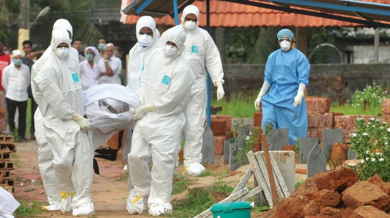 Doctors and relatives in protective dress carry the mortal remains of  a man, who died due to Nipah, to a burial ground in Kozhikode	(File pic)
