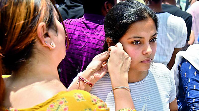 Despite instruction given to students to not wear watches and jewellery, many student still wore earings, jewellery and watches to the exam centre on Sunday. Ahead of the entering the examination centre, a mother is seen removing the earing from her daughter's ear on Sunday at the Banjara Hills Neet examination centre. (Photo: DC)