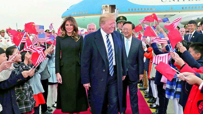 Children wave US and Chinese flags as US President Donald Trump and First Lady Melania Trump arrive at Beijing Airport on Wednesday. (Photo: AFP)