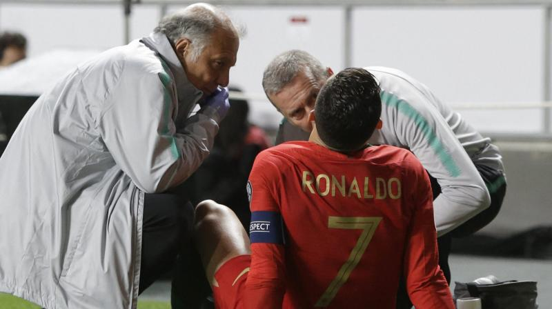 Cristiano Ronaldo receives treatment from medical staff during the Euro 2020 group B qualifying soccer match between Portugal and Serbia. (Photo: AP)