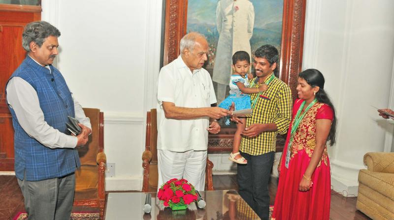 Governor presents 'visitors' certificate to a family  visiting Raj Bhavan in the company of his secretary R.Rajagopalan. (Photo: DC)