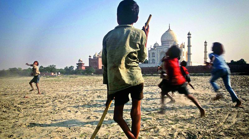 Agra, November 2003. A disabled boy watches the merriment of other children on the sandy bank of the Yamuna river opposite the Taj Mahal, the most recognised symbol of India worldwide.