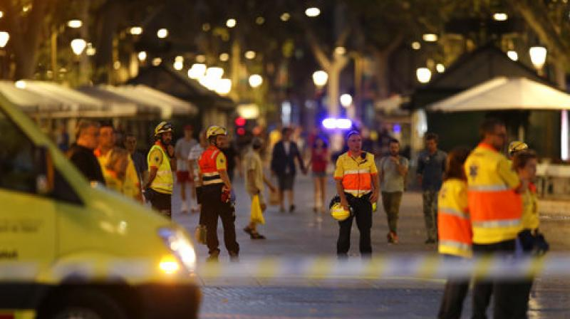 Emergency workers stand on a blocked street in Barcelona, Spain, Thursday. (Photo: AP)