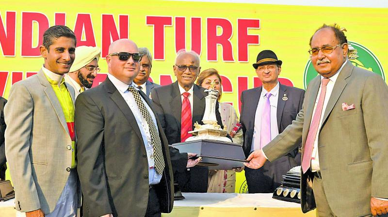 Hyderabad Race Club chairman R. Surender Reddy (centre) presents the winner's trophy to Breeder Sultan Singh (right), trainer J. E. Mckeown (second from left) and jockey Y. S. Srinath (left) after Adjudicate won the Indian Turf Invitation Cup at the Malakpet Race Course in Hyderabad on Sunday.