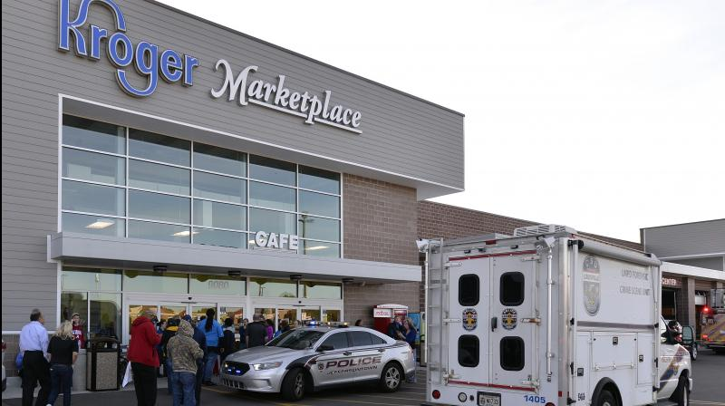 Employees wait outside the entrance of a Kroger grocery following a shooting that left two people dead and a suspect in custody on Wednesday. (Photo: AP)