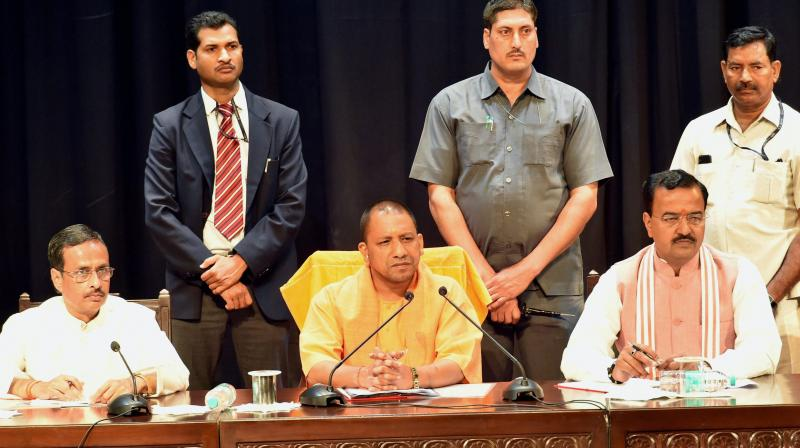 UP Chief Minister Yogi Adityanath with Deputy CMs Dinesh Sharma and Keshav Prasad Muriya at a meeting of police officers at Lok Bhawan in Lucknow. (Photo: PTI)