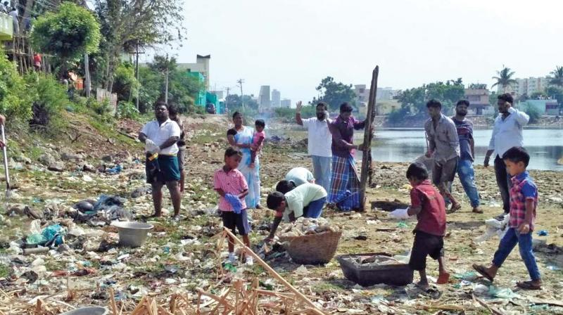 Children along with volunteers help to clean Periyakulam, a ten-acre water body at Padur, on Sunday. (Photo: DC)