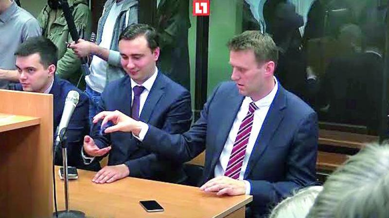 Kremlin critic Alexei Navalny posted a video of himself sitting in a court playing with a fidget spinner.