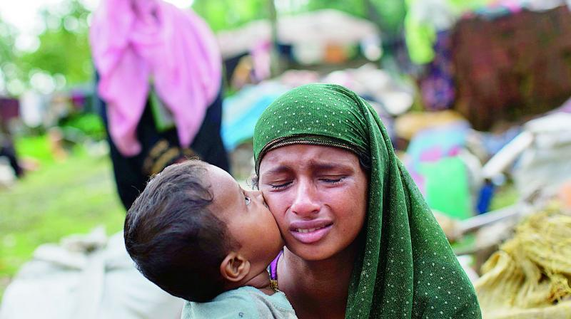 A Rohingya child kisses his mother's cheek as they rest after crossing over to Bangladesh (Photo: AP)