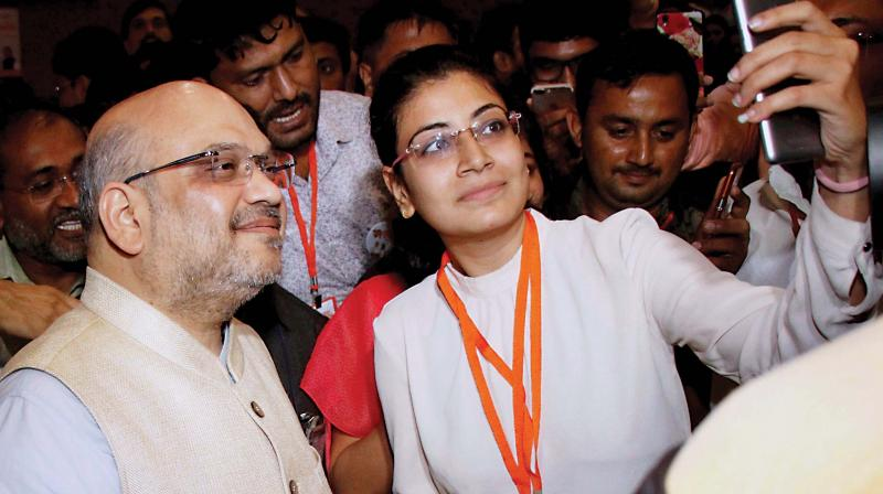 A girl takes selfie with BJP chief Amit Shah in Ahmedabad on Sunday (Photo: PTI)