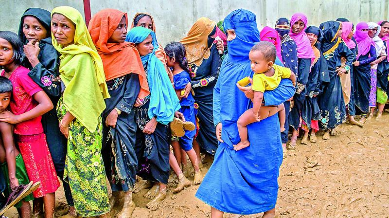 Newly arrived Rohingya women wait for their turn to collect building material for their shelters distributed by aid agencies in Kutupalong refugee camp (Photo: AP)
