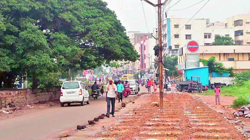 An electric pole prevents smooth flow of traffic on Shaikpet-Narsingi road (photo: DC)