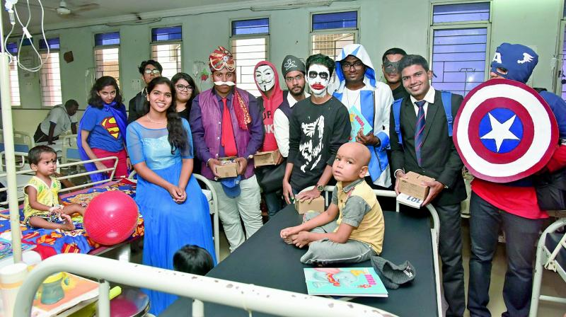Participants dressed as comic characters with kids at a hospital