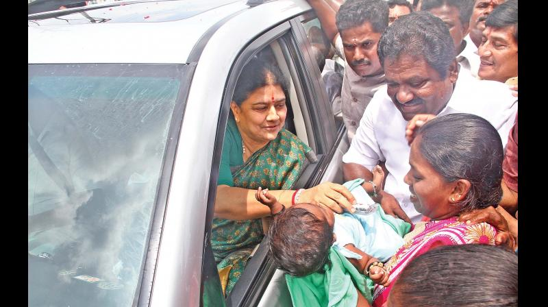 V.K. Sasikala greets a child on Wednesday on her way back after visiting her ailing husband Natarajan in the hospital (Photo: DC)