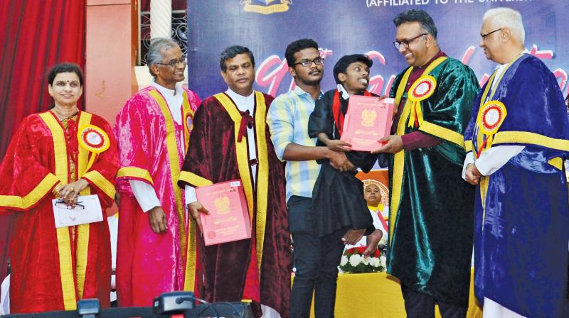 Carried by his kind roommate Immanuel, dwarf S Vincent is all smiles as he receives his medal and the B.A. (History) degree from chief guest Prof C. Raj Kumar, Founding Vice-Chancellor, O P Jindal Global University. (Image DC)