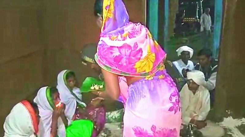 Women swallow lit lamps at a ritual held  at the village headman's house in Kanchanpalli.