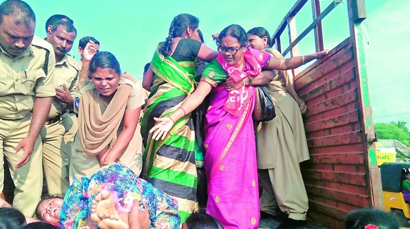 A protesting woman is pushed on to a truck by police personnel, to be arrested. She was protesting during the funeral procession of E. Ravinder