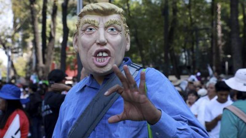 A man wears a mask depicting U.S. President Donald Trump during a march demanding respect for Mexico and its migrants, in the face of perceived hostility from the Trump administration, in Mexico City. (Photo: AP)