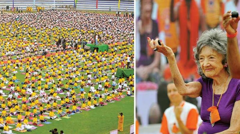From Left, volunteers perform Yoga asanas and 98-year-old yoga practitioner, Tao Por Tin Lynch from United States  at Sri Kanteerava Stadium in Bengaluru on the occasion of 3rd edition of International Yoga Day on Wednesday  —Shashidhar B