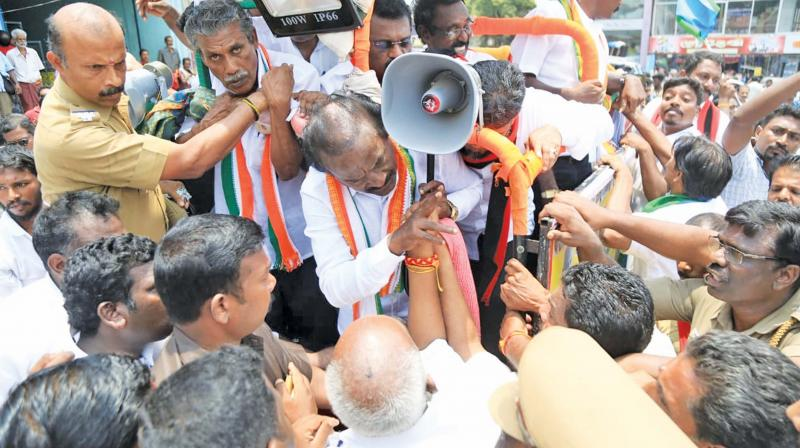 BJP candidate Pon Radhakrishnan reaching out to his rival Congress candidate H Vasanthakumar in his attempt to prevent a possible clash between the Congress and the BJP cadres during the elction campaign at Nagercoil in Kanyakumari constituency on Wednesday. (Photo: M Aruloli)