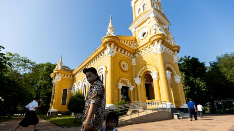 The church, which is painted yellow and rises up off land by the river, is proud of its historic role in spreading the faith. (Photo: AFP)