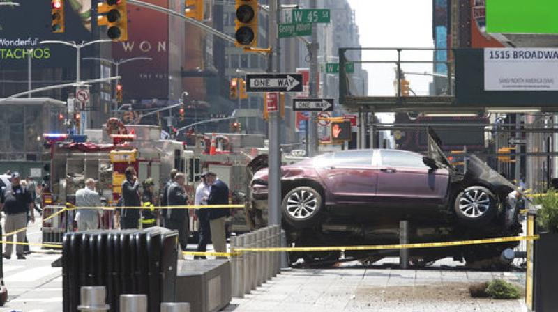 A car rests on a security barrier in New York's Times Square after driving through a crowd of pedestrians, injuring at least a dozen people. (Photo: AP)