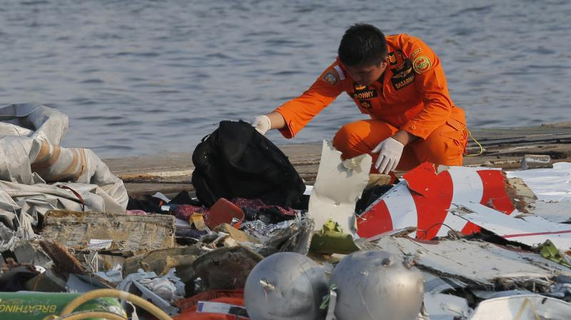 A member of Indonesian Search and Rescue Agency (BASARNAS) inspects debris believed to be from Lion Air passenger jet that crashed off Java Island at Tanjung Priok Port in Jakarta, Indonesia Monday, Oct. 29, 2018. (Photo: AP)