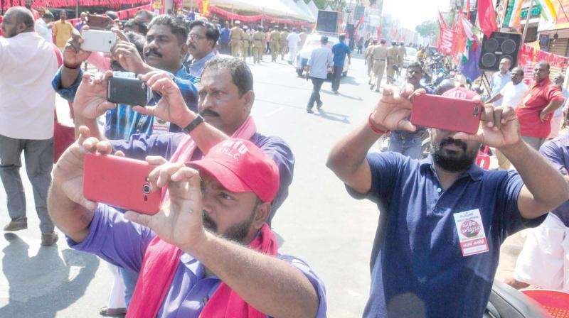 CITU activists capture images of the rally being taken out along the MG Road in front of the Secretariat on Tuesday, expressing solidarity with the two-day all-India general strike. In the background is the huge shamiana covering half the road up to the divider, erected by the organizers in flagrant violation of the court order against blocking roads.  Union leaders took turns, addressing the public meeting of strikers seated under the shamiana. Chief Minister Pinarayi Vijayan and ministers kept off the Secretariat. (Photo: A.V. Muzafar)