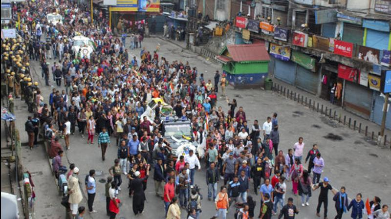 Activists of Gorkha Janmukti Morcha (GJM) take out a funeral procession with the bodies of their three activists who were killed Saturday. (Photo: PTI)