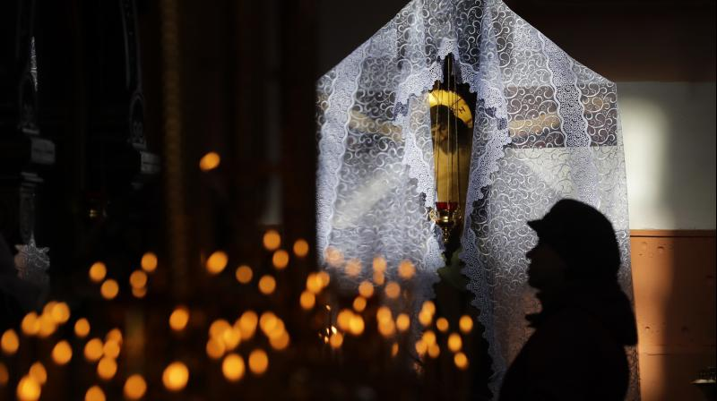 The crucifix is illuminated by sunlight as woman prays during a service on the eve of Easter. (Photo: AP)