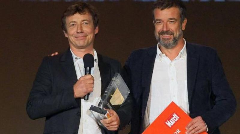 French photographer Laurent Van der Stockt (left) receives the Paris Match Visa d'Or award in the news category from Paris Match deputy director Regis Le Sommier on Sept 9, 2017. (Photo: AFP)