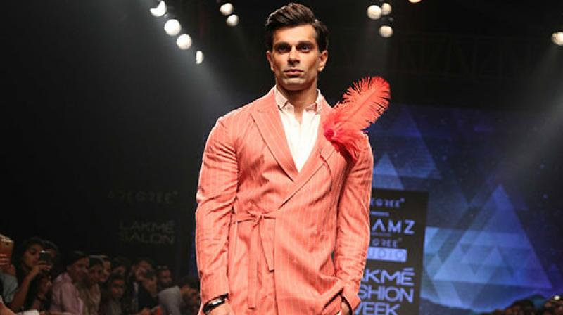 Karan Singh Grover, the showstopper for the designers, sported a bright peach suit with intricate embroidery, accessorised with a bright red feather.
