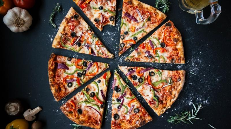 To get free pizza, a group of at least four people have to eat pizza at the restaurant.  (Photo: File)