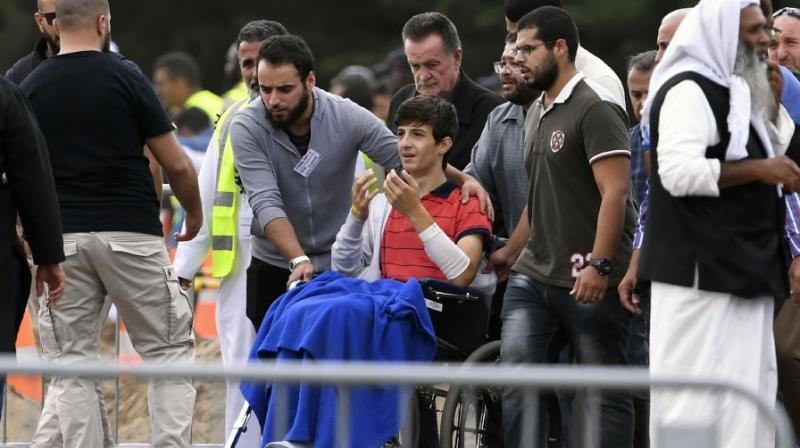 Zaid Mustafa (centre, in wheelchair), who was wounded by an Australian white supremacist gunman, attends the funeral of his slain father Khalid Mustafa and brother Hamza Mustafa at the Memorial Park cemetery in Christchurch on March 20, 2019. (Photo: AFP)