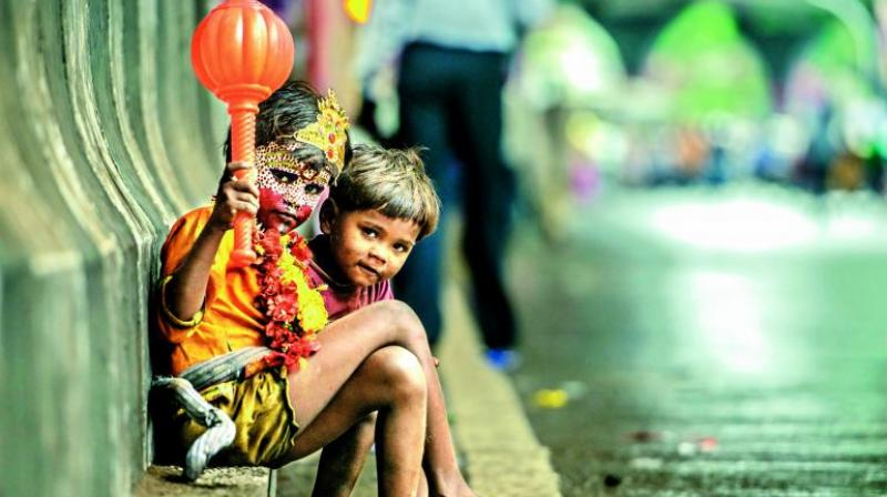 Kids sitting on a road outside a Ganpati pandaal dressed as Gods, expecting money from the devotees.
