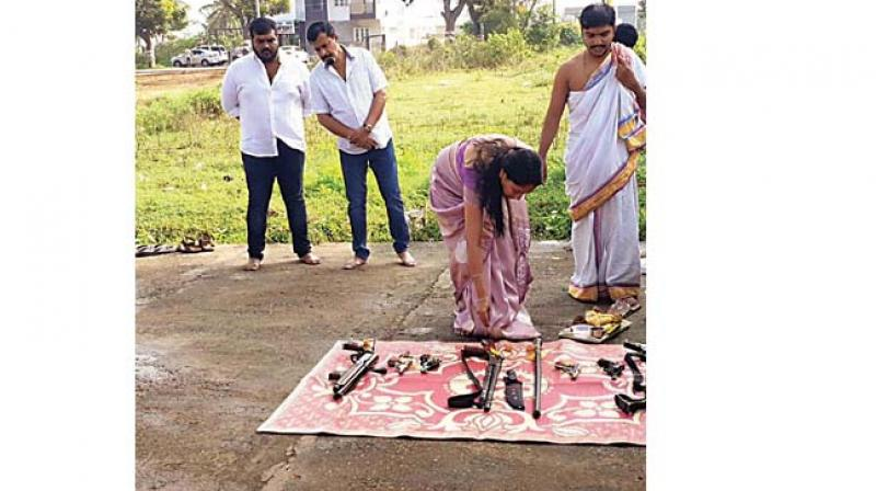 A family member of Jaya Karnataka chief Muthappa Rai performs puja for guns and other lethal weapons, as  Rai (second from left) looks on