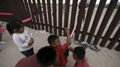 Children plays on a seesaw installed between the steel fence that divides Mexico from the United States in Ciudad de Juarez, Mexico, Sunday. The seesaw was designed by Ronald Rael, a professor of architecture in California. (Photo: AP)