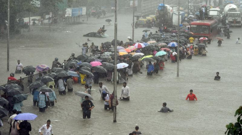 Heavy rains Tuesday brought Mumbai to a halt flooding vast areas of the city. People were stranded for hours as train services were halted and water levels kept creeping up. (Photo: AP/PTI)