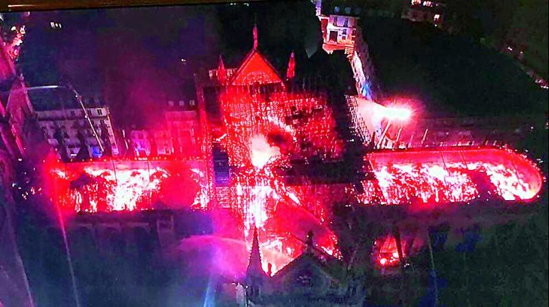 A image captured by a drone of the Notre Dame cathedral on fire. (right) Flames and smoke rise as the spire of Notre Dame cathedral  collapses in Paris on Monday. 	(Photo:  AP)