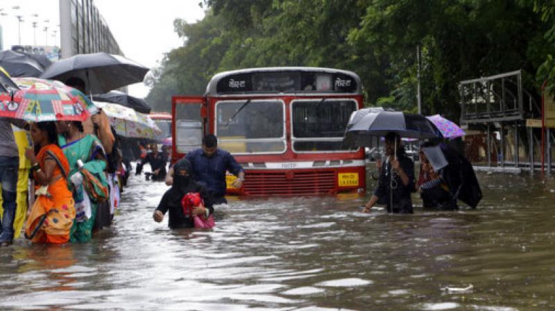 People walk through a waterlogged street following heavy rains in Mumbai. (Photo: AP)