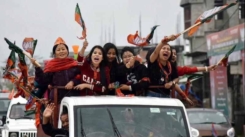 Supporters of BJP wave their flags as they celebrate their candidate win Assembly elections in Imphal. (Photo: PTI)