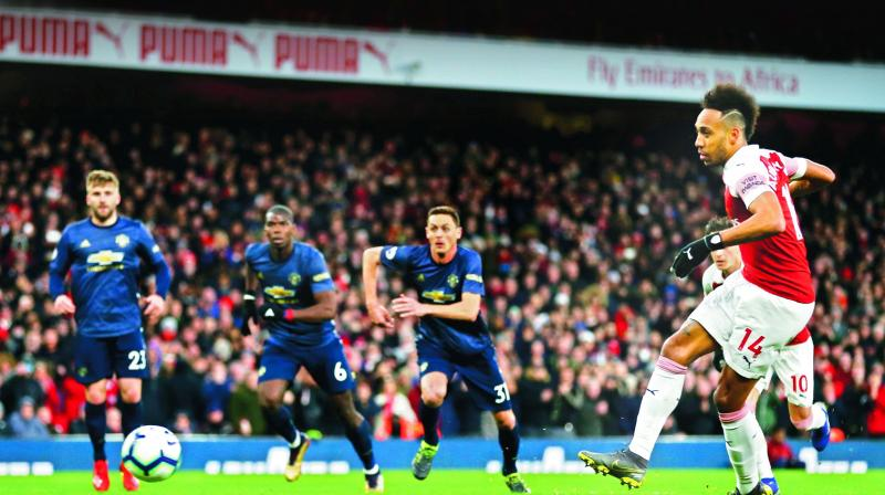 Arsenal's Pierre-Emerick Aubameyang (right) scores against Manchester United in their EPL match at the Emirates Stadium in London on Sunday. (Photo: AFP)