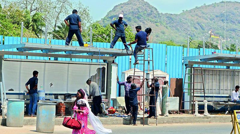 Workers instal a swanky new bus shelter in Vijayawada on Monday.